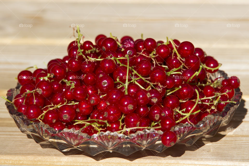 Red currant on glass dish placed on wood