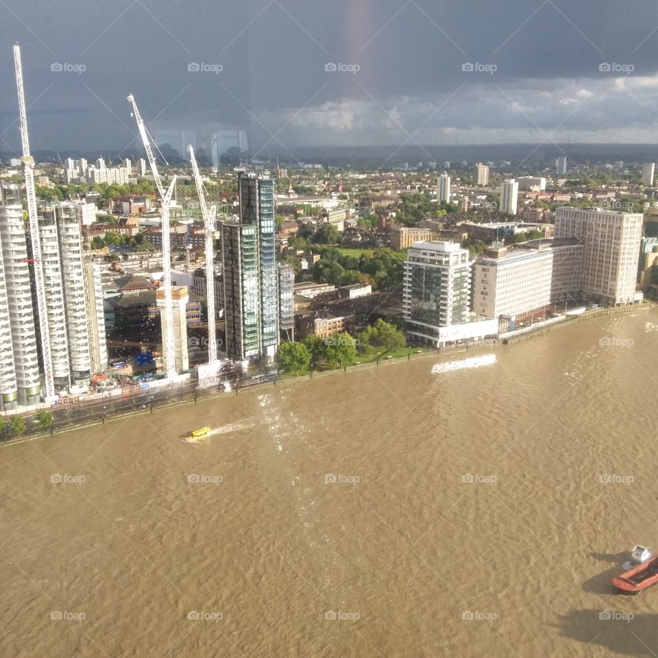 A view of London city skyline from above featuring River Thames and boats