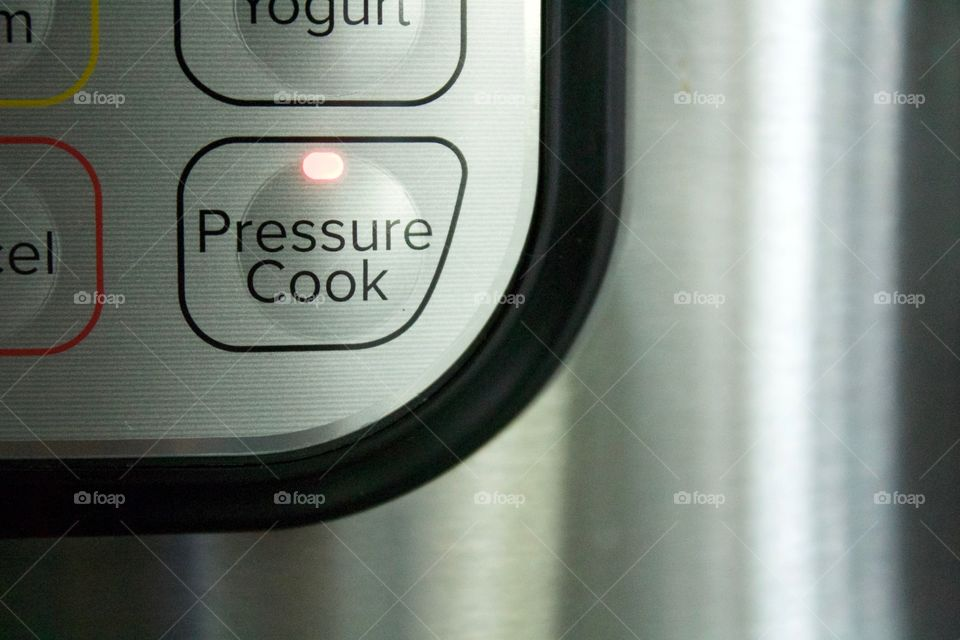 LED lIght on an electric pressure cooker control panel button showing that the pressure cooking option has been selected