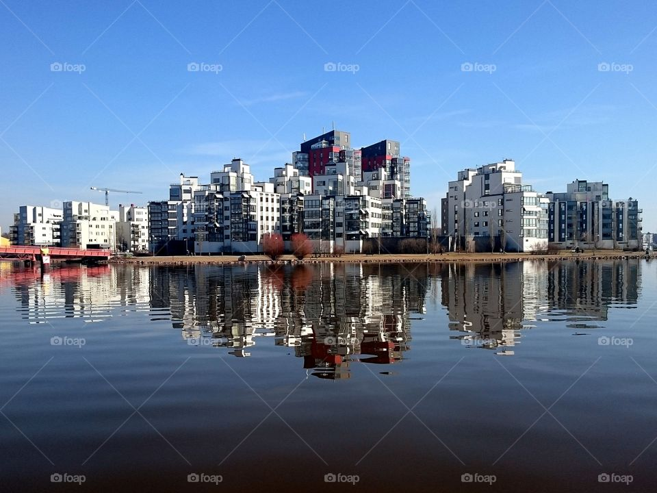 City reflection. Small skyscrapers reflects in the water