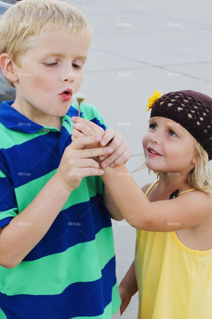 Super sweet photo of two children holding hands and playing with a dandelion they found!!