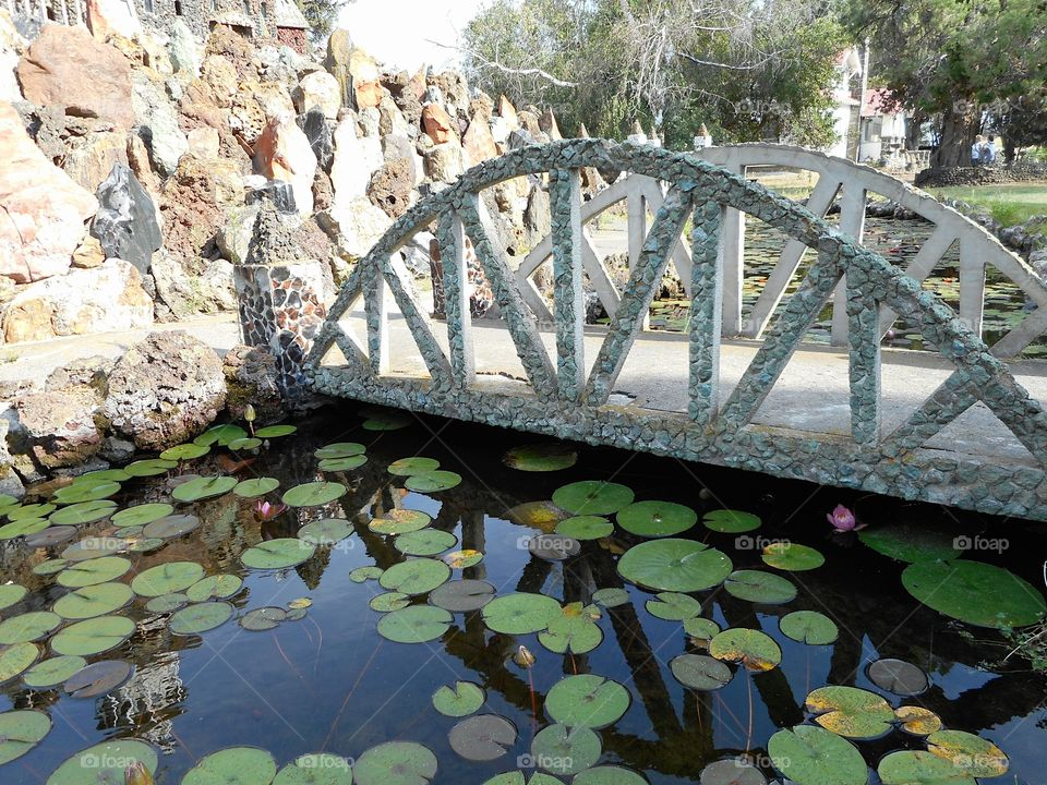 A beautiful and ornate rock bridge on a peaceful path crosses a fairytale style mote with lots of Lillie Pads at Peterson's Rock Garden on a sunny summer day in Central Oregon.