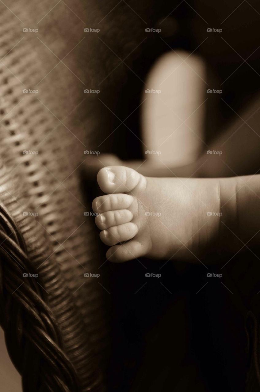 Baby feet in sepia tones on wicker basket