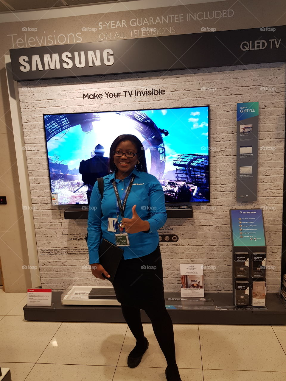 Woman posing in front of the Samsung QLED television 4K UHD TV with soundbar