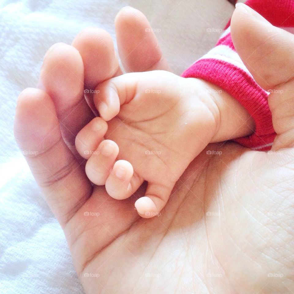 Mother's hand holding babies hand