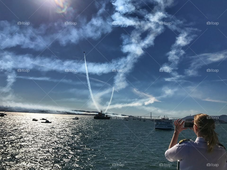 A photographer taking some cell phone pics during fleet week in San Francisco, CA.