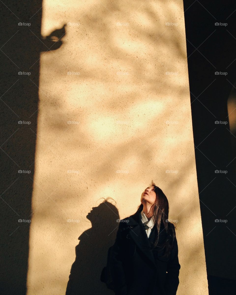 Woman standing against wall and looking up with shadow