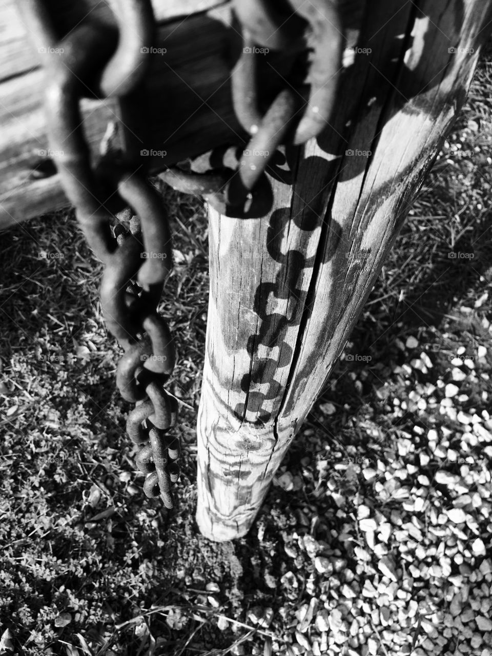 Rusted chain resting on weathered fence waiting for the next opportunity to work