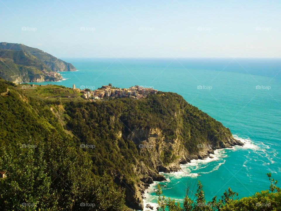 Spectacular view of the Mediterranean sea's turquoise waters from a cliff in Riomaggiore, region of Liguria in Italy. View of Cinque Terre village at a distance.