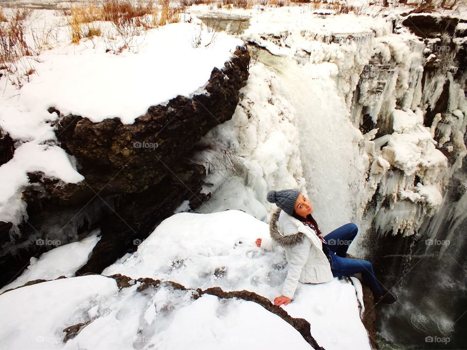 Girl sitting by the frozen icy Waterfall