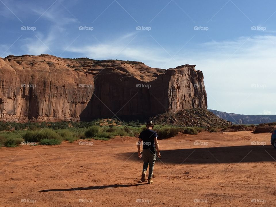 Man walks in the desert of the monument valley