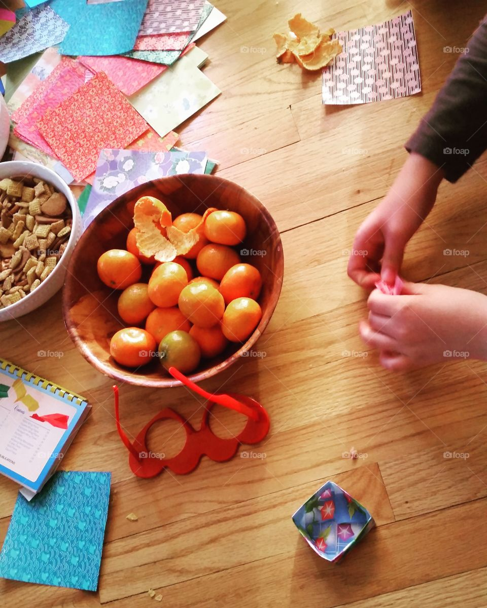 person completing craft project with bowls of snacks