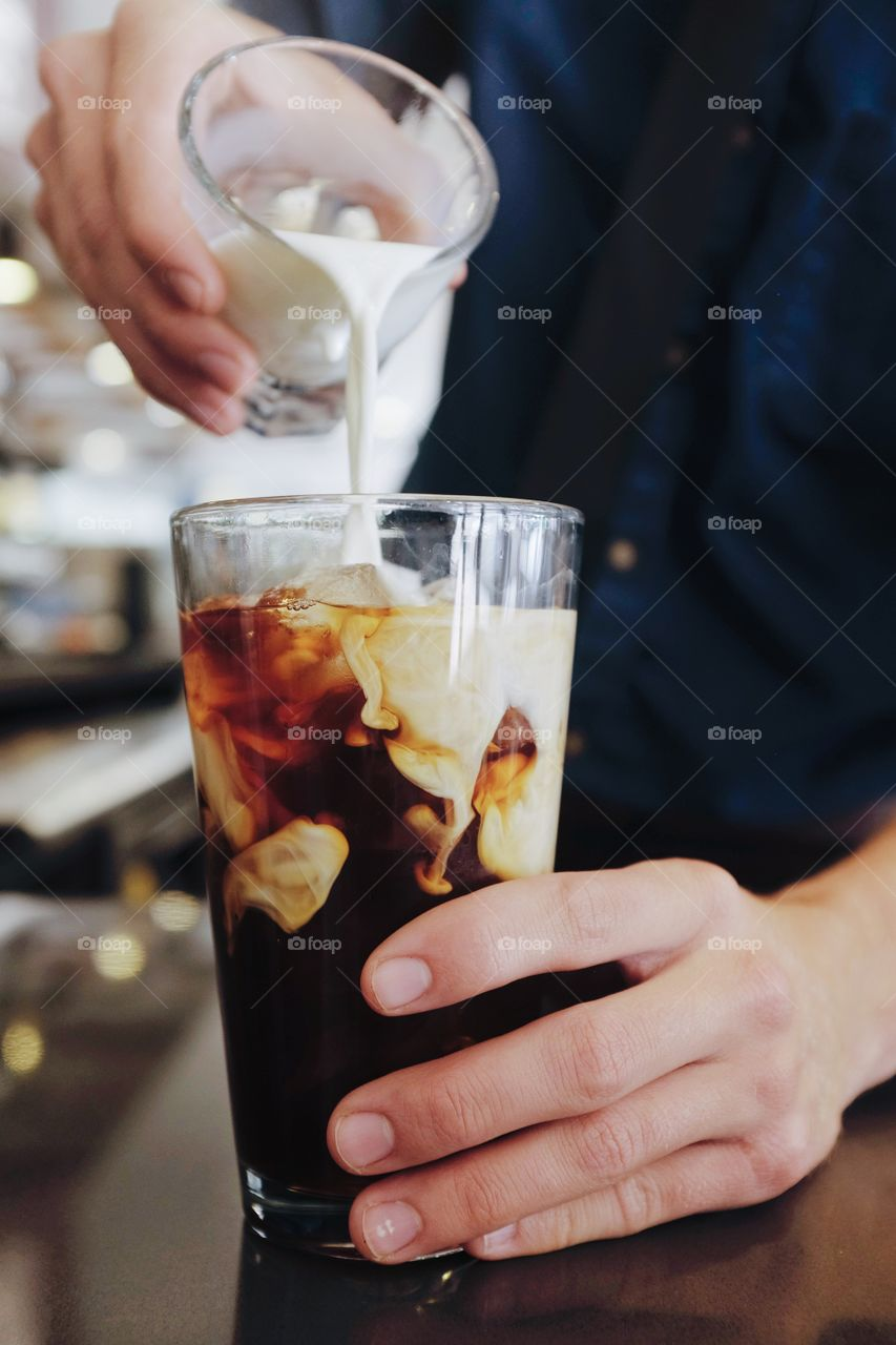 Person's hand pouring milk over iced coffee