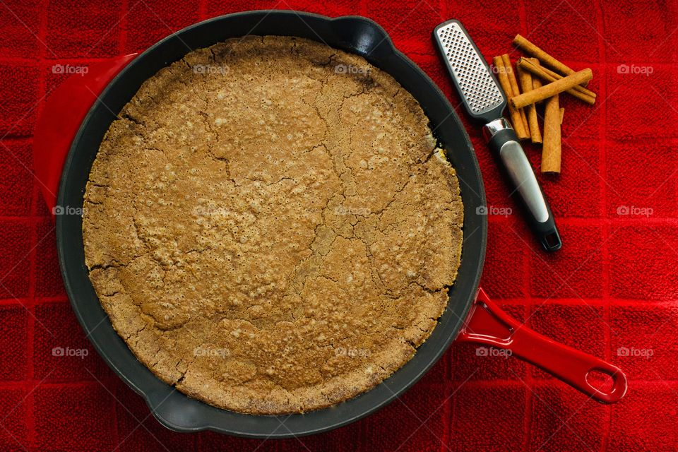 Overhead view of a freshly baked Cinnamon Sourdough Dutch Baby in a red cast iron skillet with cinnamon sticks and mini-grater on a red towel