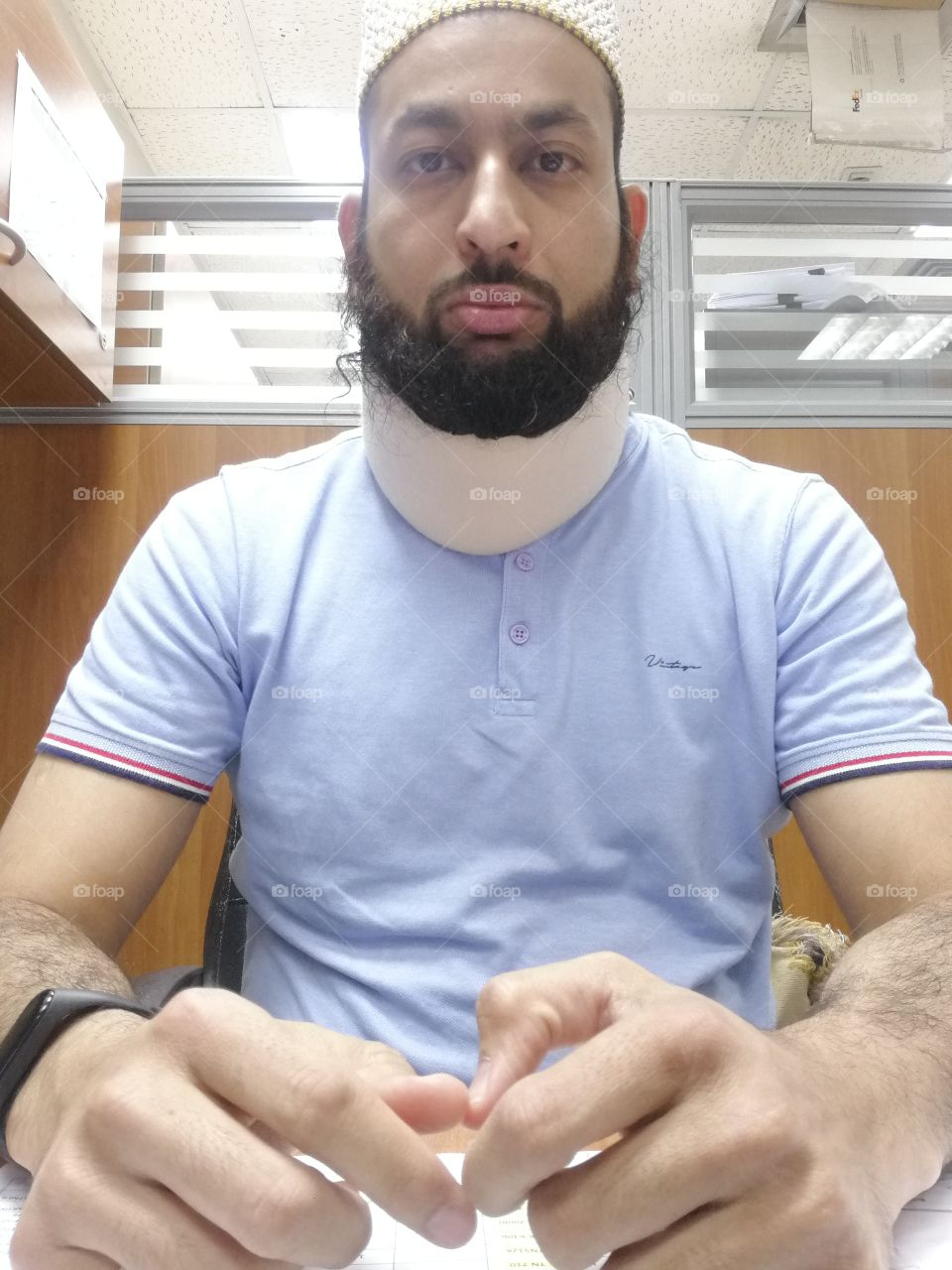 Young Bearded man in tshirt with neck pain collar and fitness band