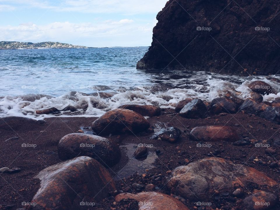 Ocean water flowing over rocks. Waves lightly crashing on a peaceful Mediterranean beach in the south of France