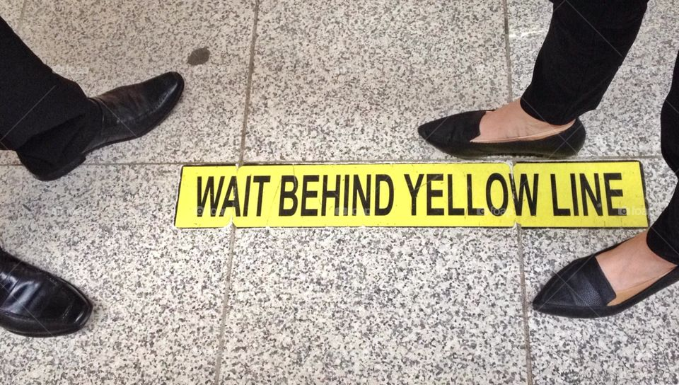 Stand behind yellow line sign