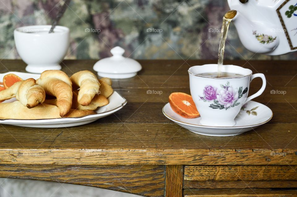 Tea and crescent rolls on wood table