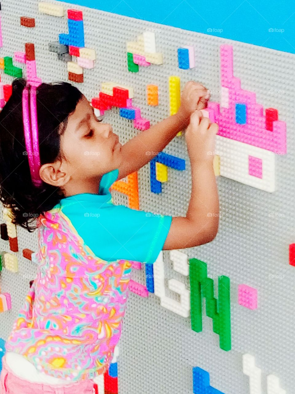 Little girl continues building lego bricks, making a pink house