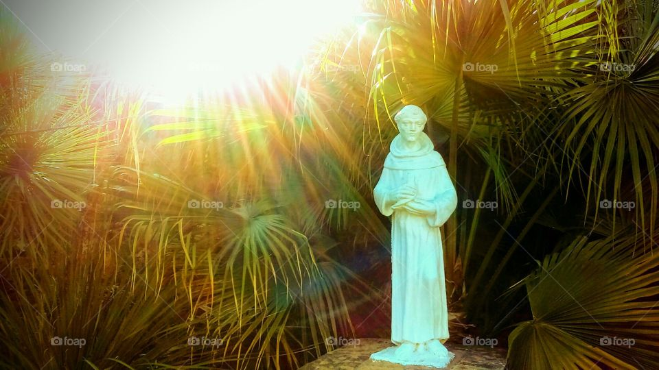 Saint Francis Of Assisi Statue with sun rays shining down on him at sunset