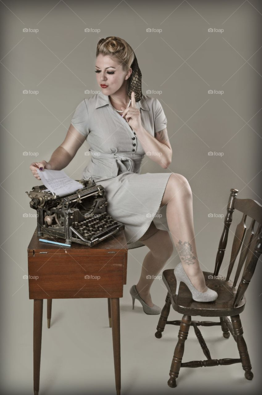 Retro woman sitting on desk holding paper