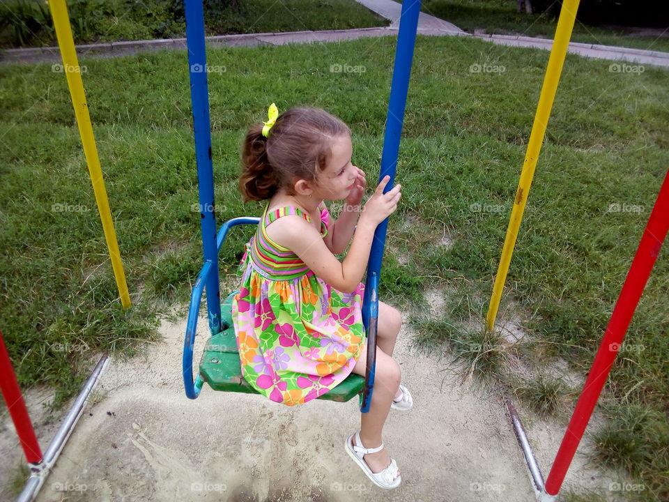 Little nice girl on the swing boat