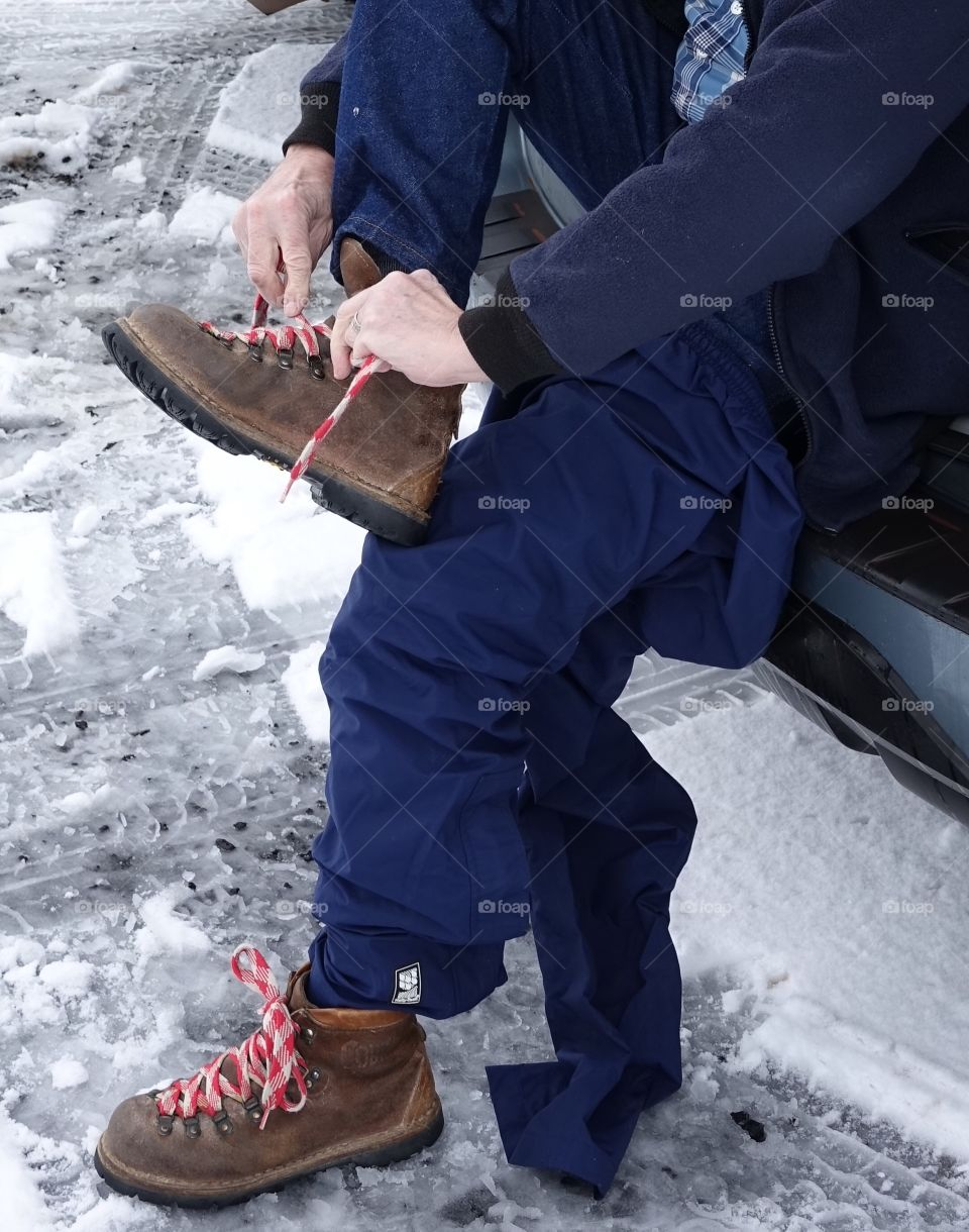 Pulling on boots off the back of a car to go play in the snow.