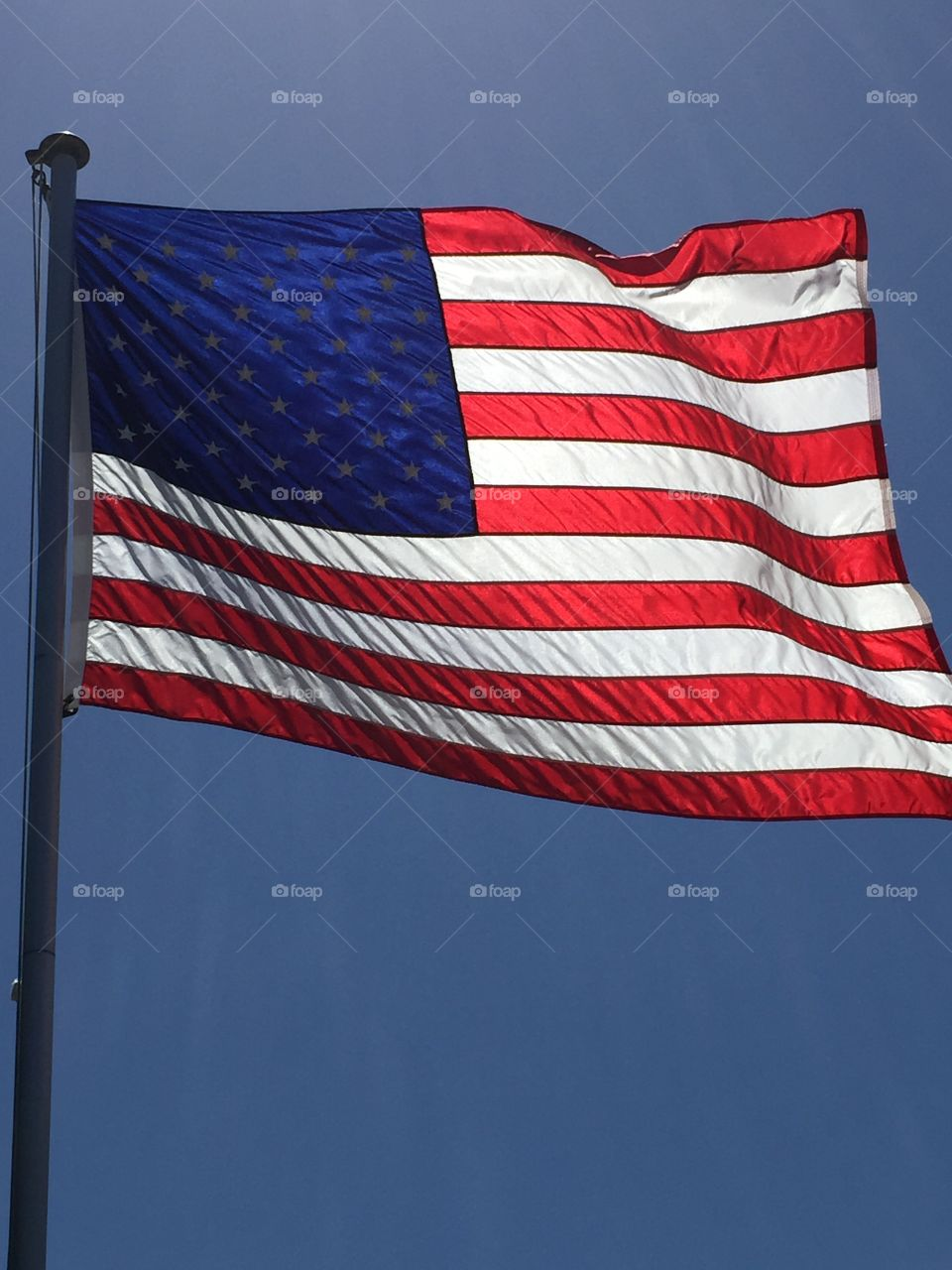 American flag. American flag blowing in the wind backlit
