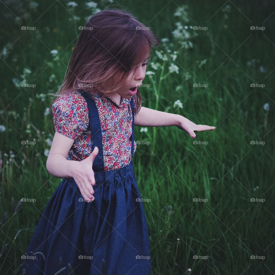 Surprise!. Lucy's look of delight at discovering a huge patch of dandelions ready to blow and make wishes.