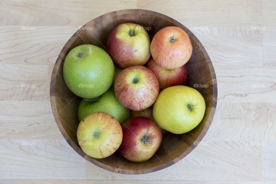 Apples different colors in wood bowl, from above