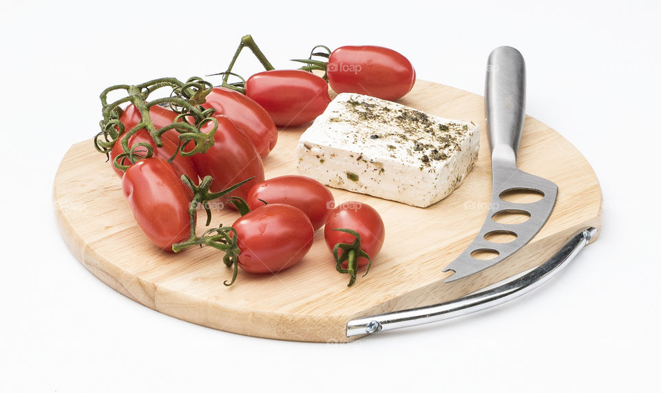 Savoury Roma tomatoes, feta  cheese and knife on a cutting board  isolated against a white bacground.