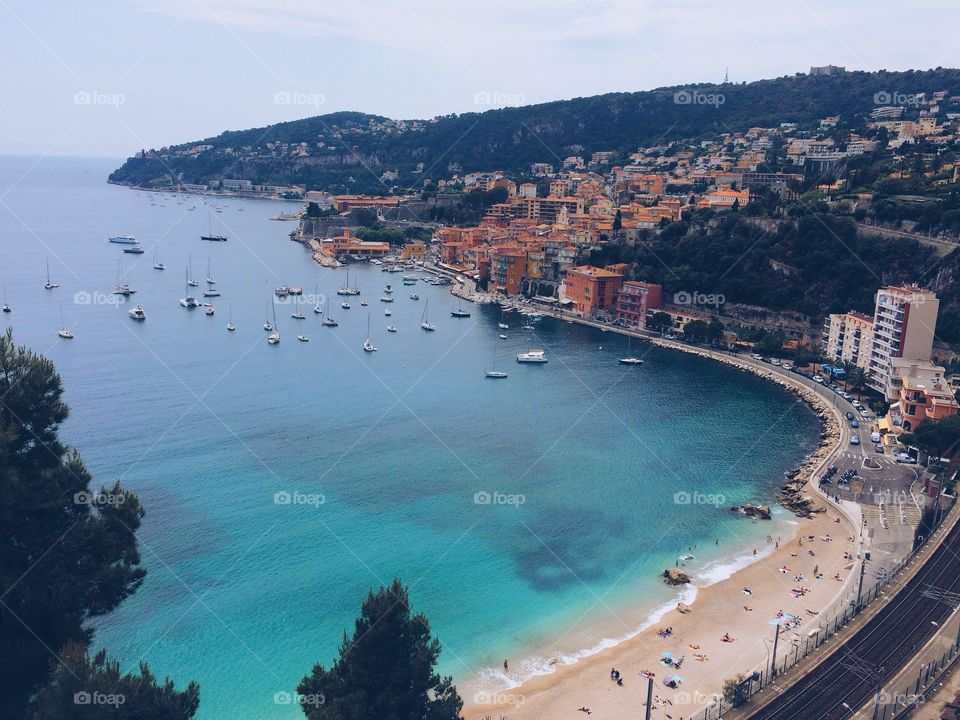 Bay on the French Riviera with beach and town. Overlook of sailboats and beach in a with calm blue water in south France.
