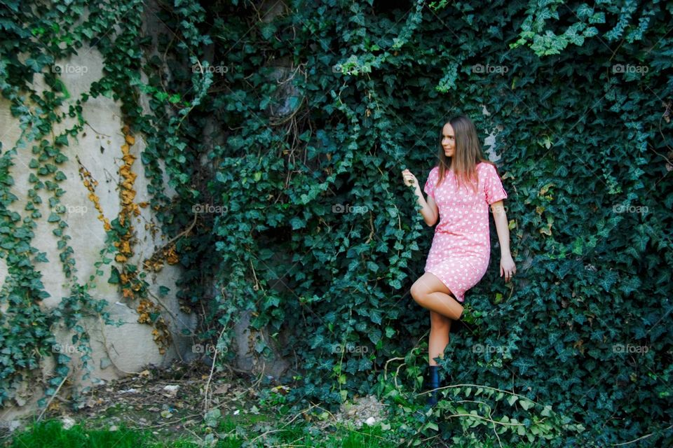 Woman in pink dress standing against poison ivy wall