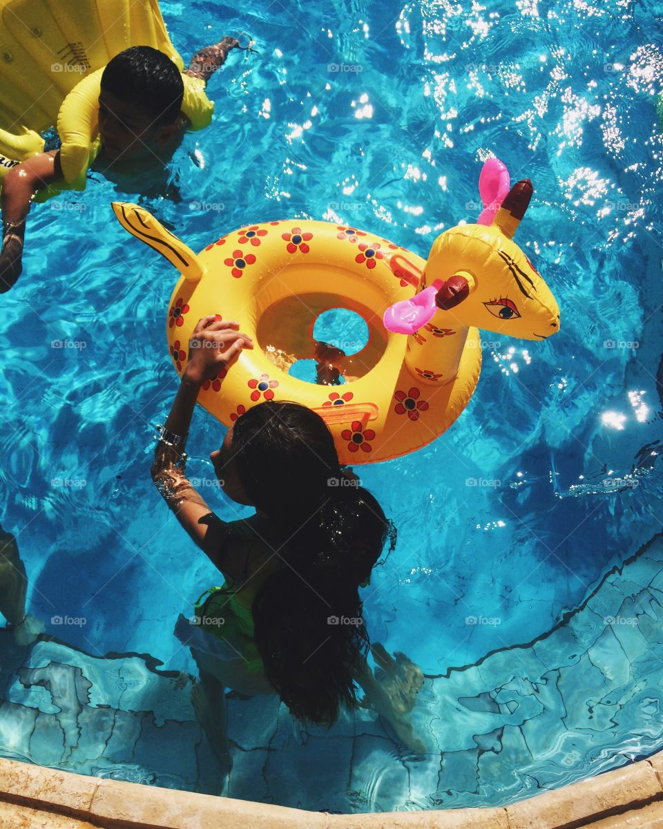 Elevated view of children playing with inflatable tube in swimming pool