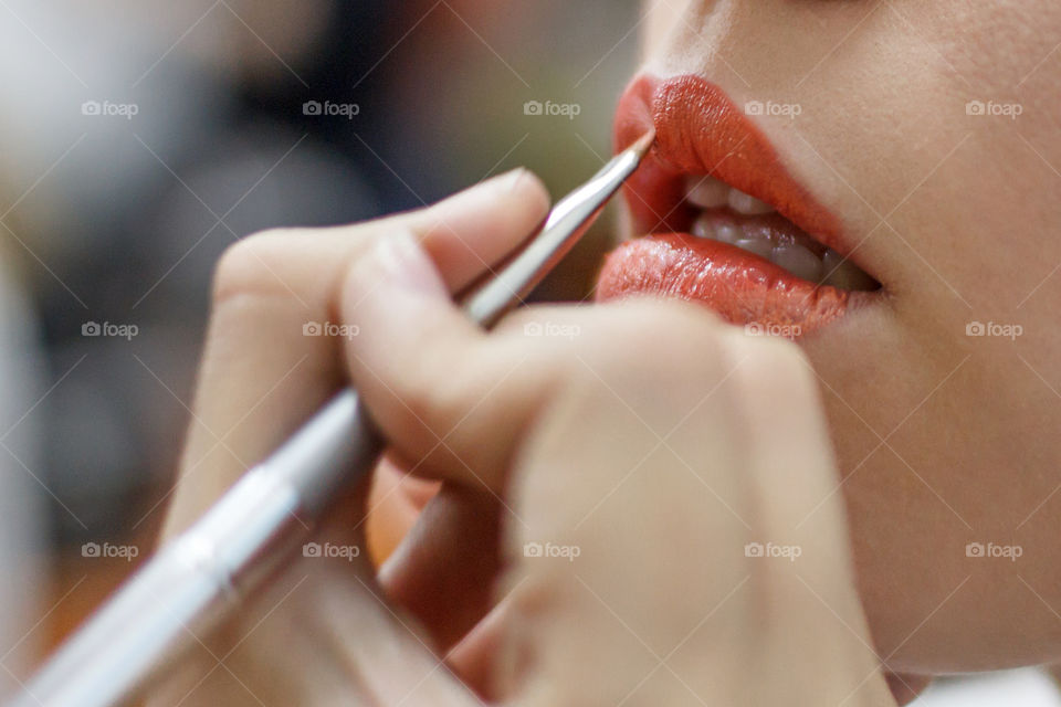 Girl paints lips with lipstick