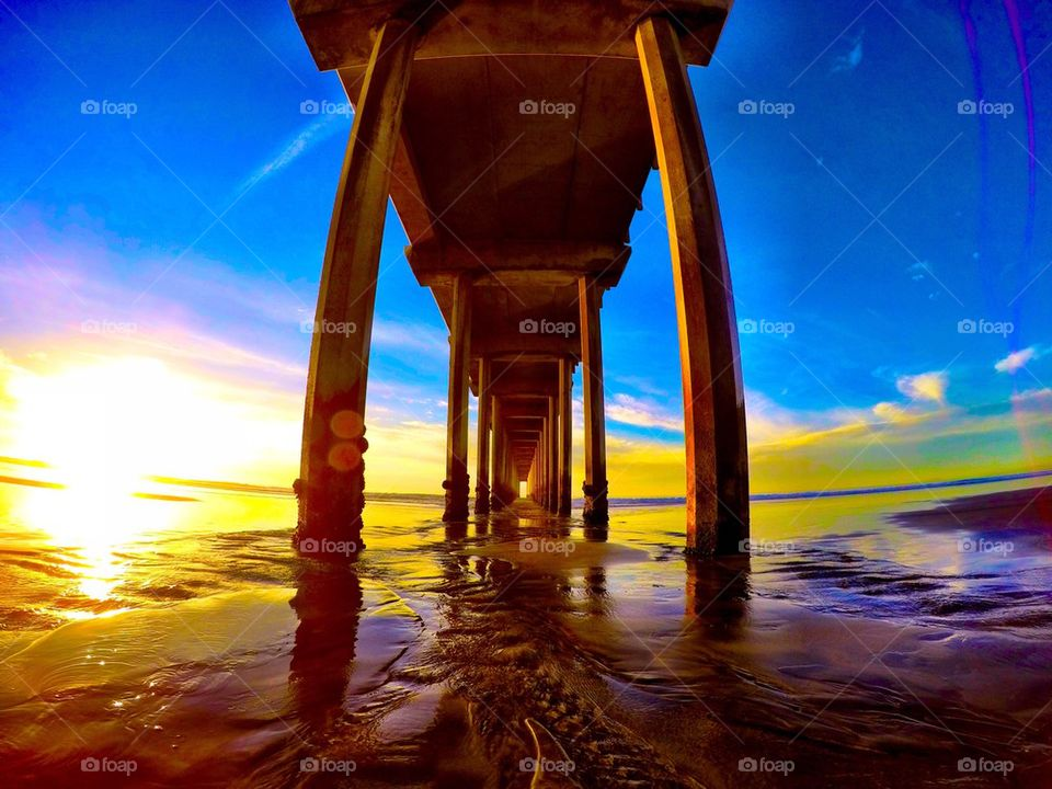 Low angle view of pier in sea at sunset