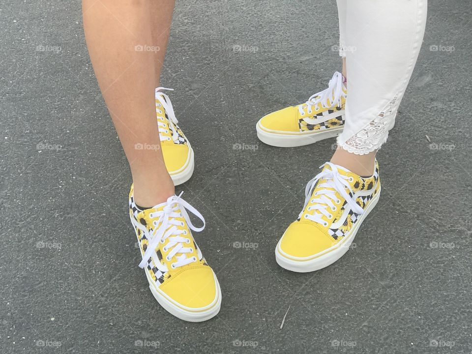 Best friends matching bright yellow shoes