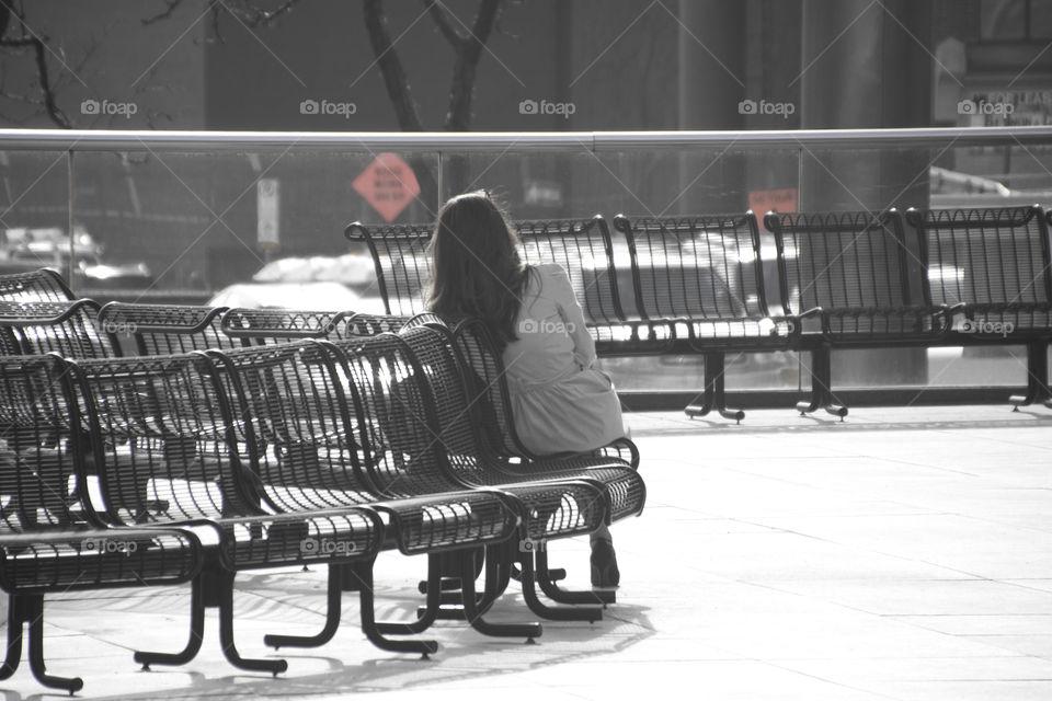 Women sitting alone, back and white, waiting
