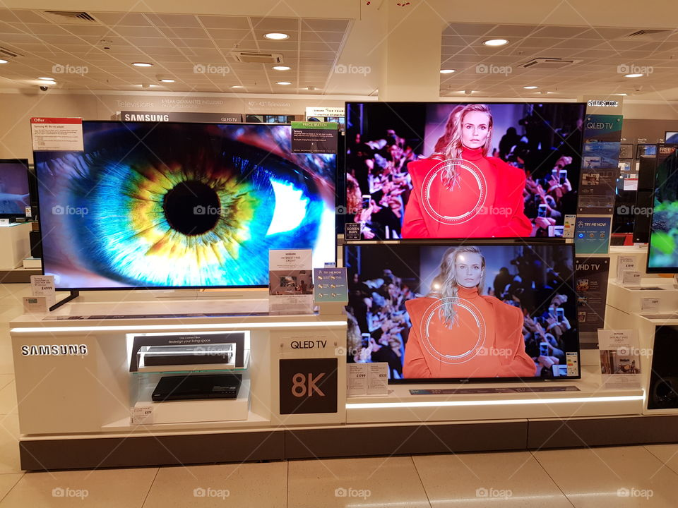Samsung 8K QLED television blue eyes demo on QLED television and comparison wall with model