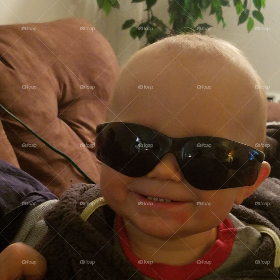 A little boy with black sunglasses