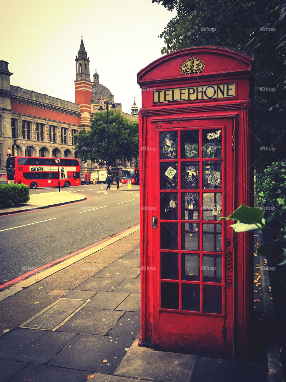 You are in London. Red telephone box and bus by the Victoria and Albert Museum, South Kensington, England.