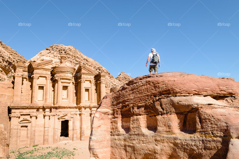 Young man traveler on the rock while observing Petra ancient monument, blue sky, travel