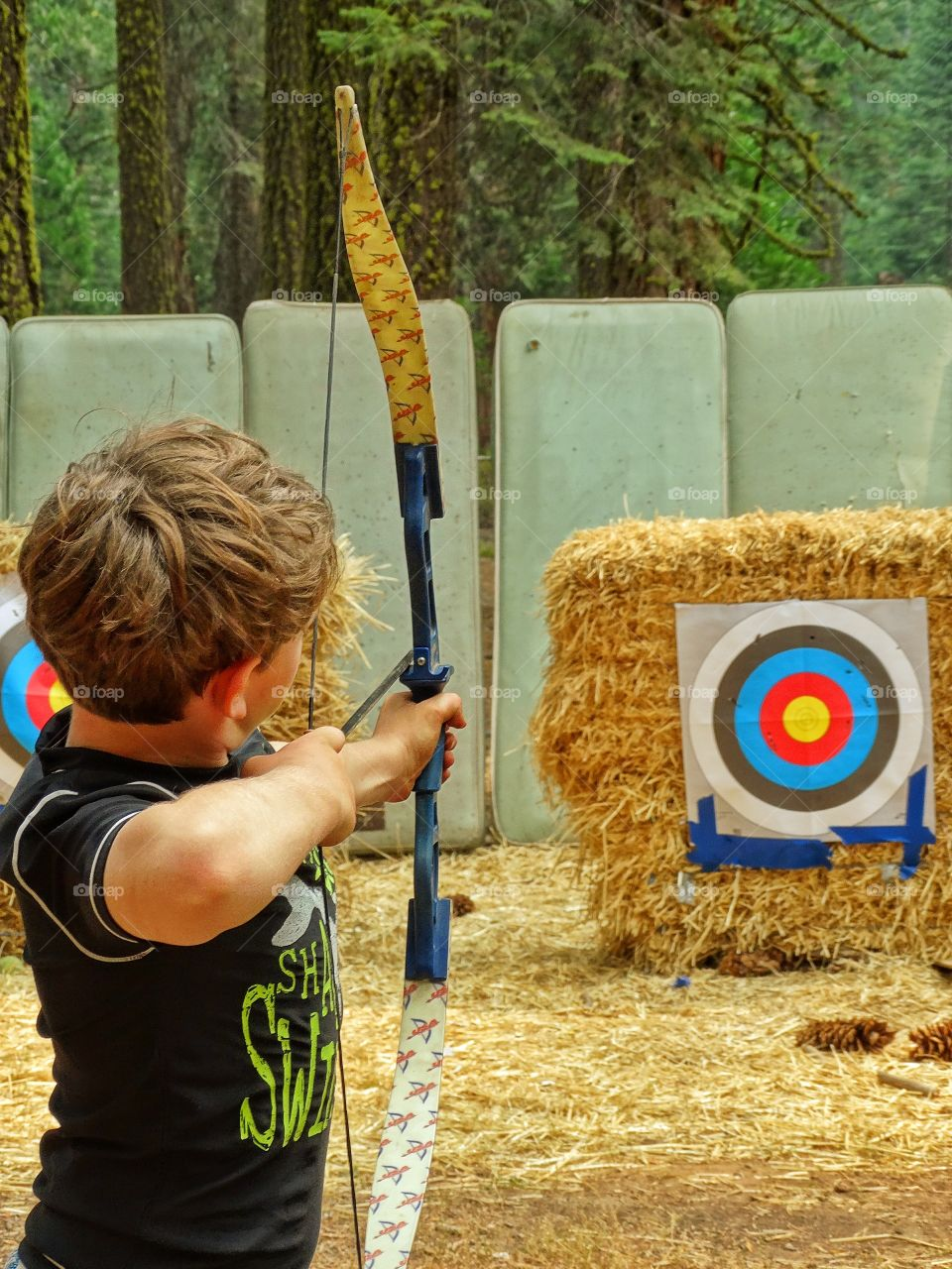 Boy Shooting Arrows. Target Practice At The Archery Range