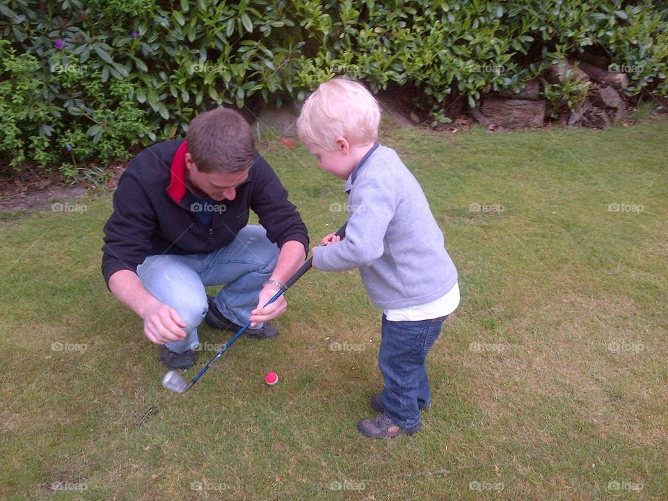 Young boy learning golf