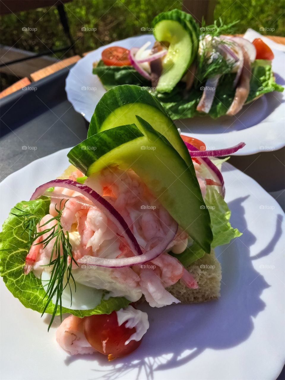 Sandwich with peeled shrimps and vegetables in foreground on white plate outdoors in garden cafe.