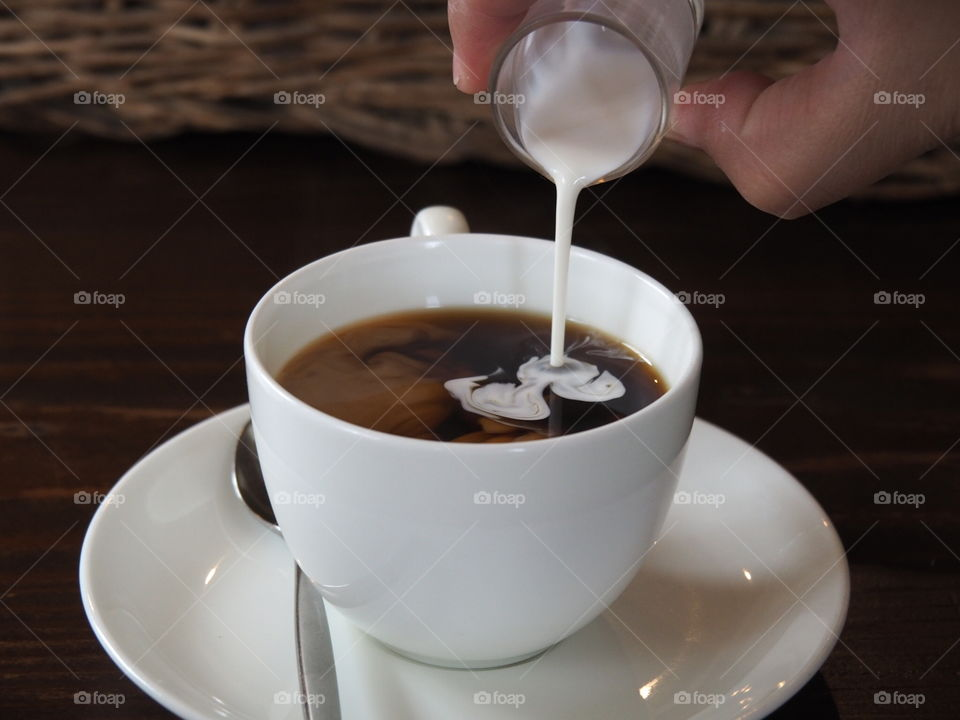 Pouring fresh milk in coffee. The moment of pouring milk in a cup of coffee. It's like freezing time to see how it looks like on the surface of the coffee when we pour the milk in.