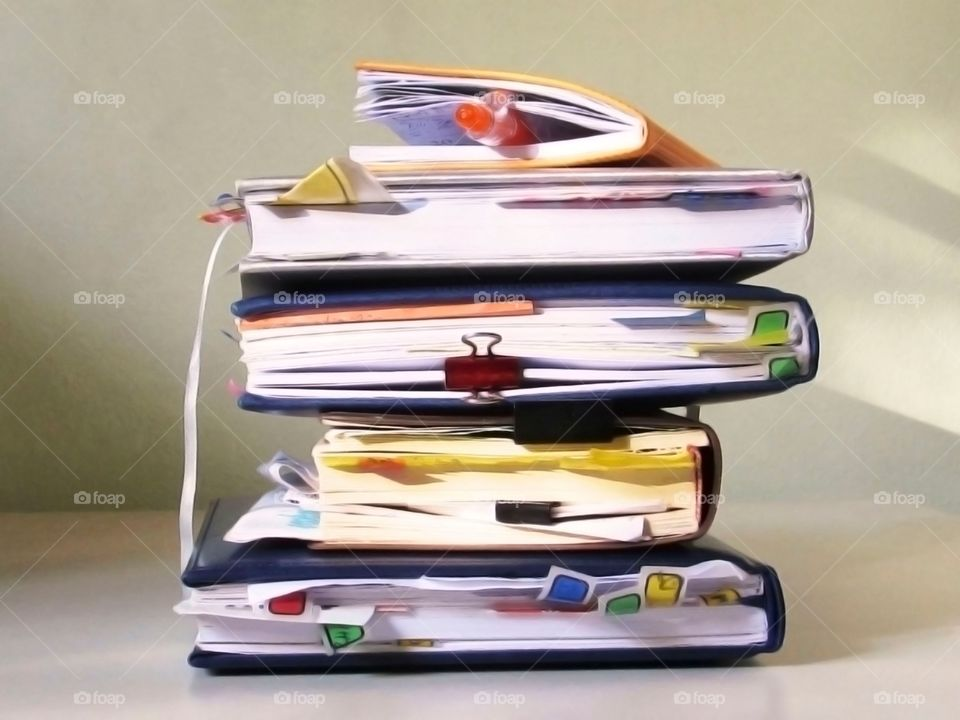 Stack of hardcover books bookmarked with stationery