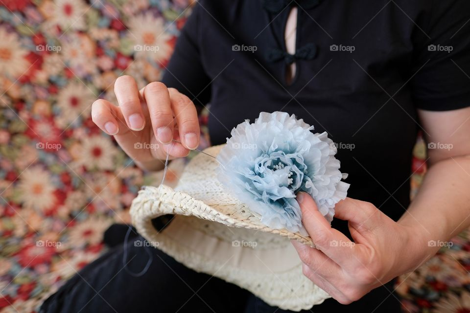 Close-up of hands sawing a blue silk flower on a straw hat.