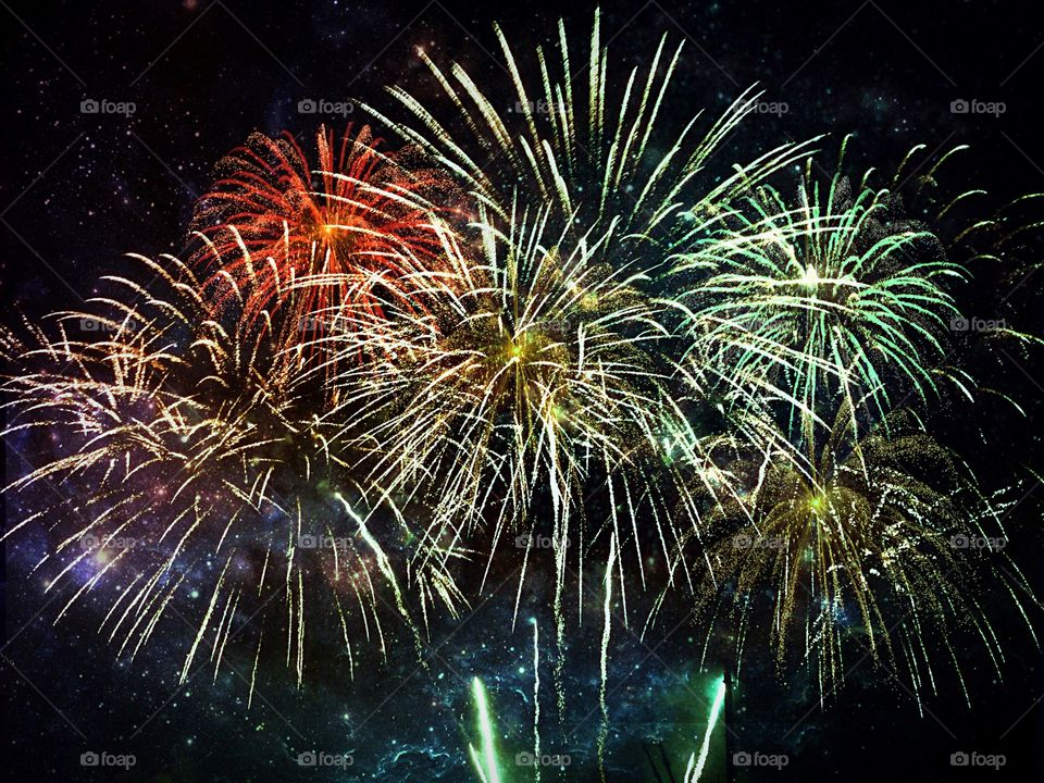 Fireworks in candy colors fill the night sky.