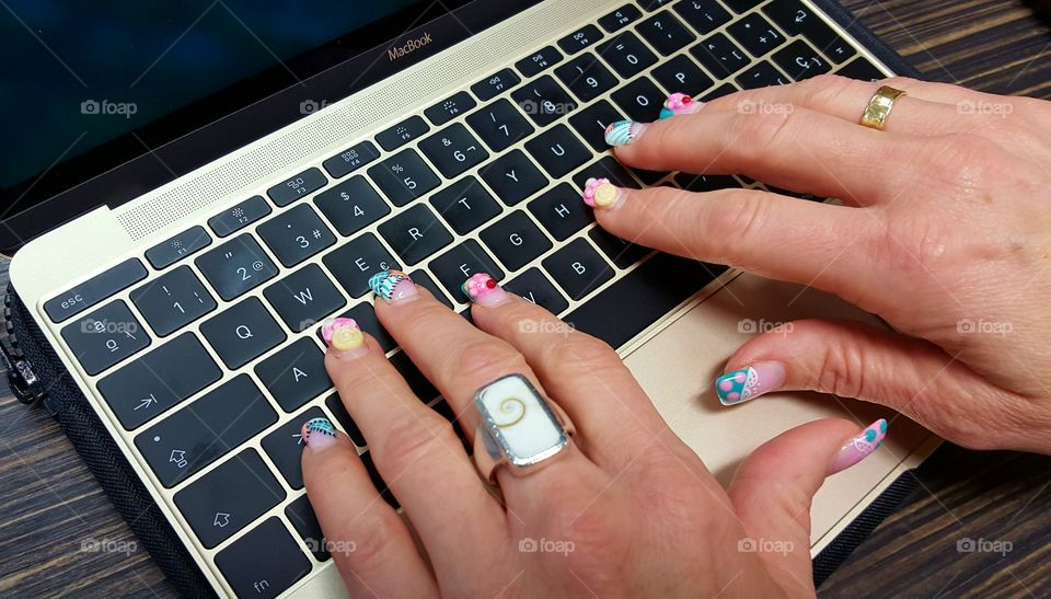 Fancy nails working on a Macbook